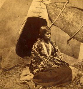 Native American woman outside her wigwam